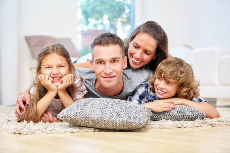 Portrait Of Happy Family Lying On Floor At Home