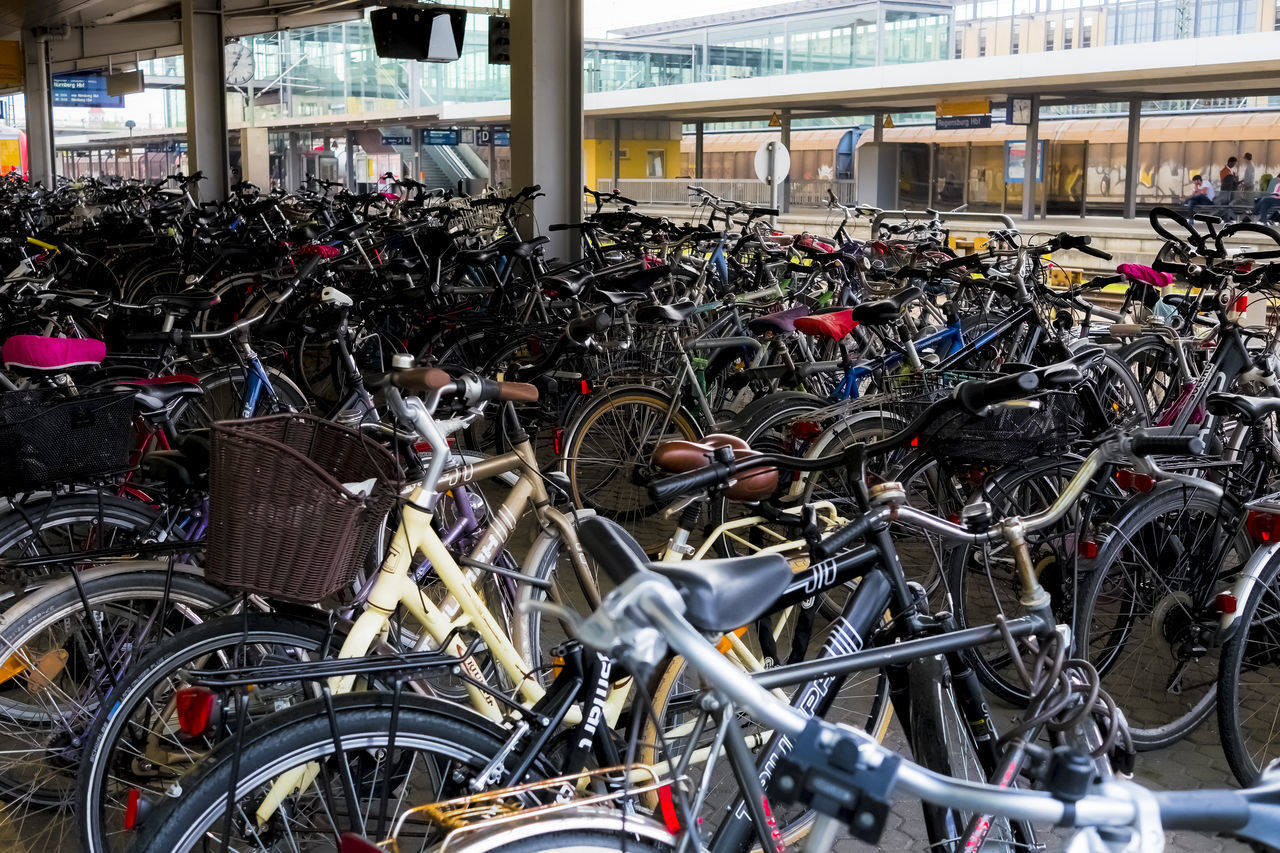 bicycle, land vehicle, mode of transportation, transportation, stationary, architecture, no people, day, large group of objects, parking lot, built structure, city, outdoors, abundance, parking, junkyard, building exterior, metal, travel, abandoned, wheel, consumerism, bicycle shop