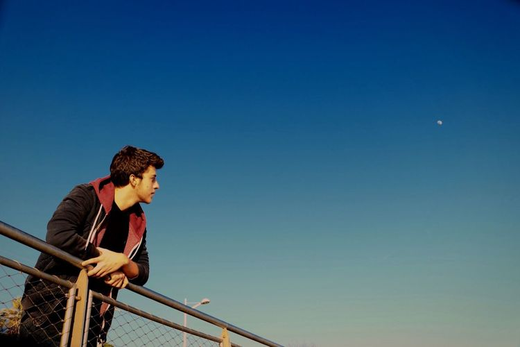 Low angle view of young man leaning on railing against clear sky