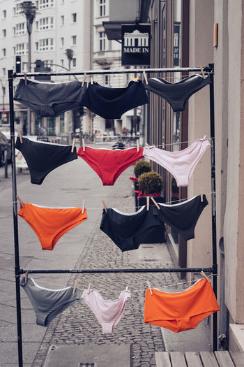 Building Exterior Day Architecture City Built Structure No People Outdoors Red Focus On Foreground Table Hanging Chair Nature Textile Flag Building Street Transportation Sunlight Shorts Underwear😈