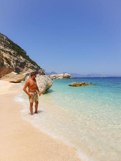 Shirtless man looking away while standing at beach