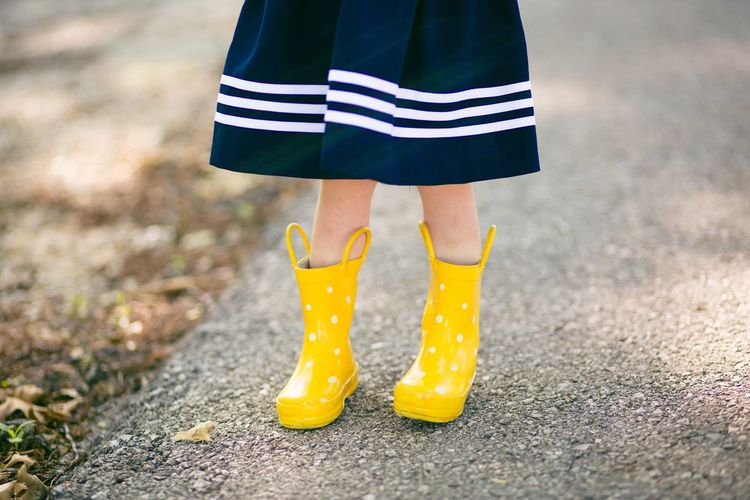 Low section of girl wearing rubber boots