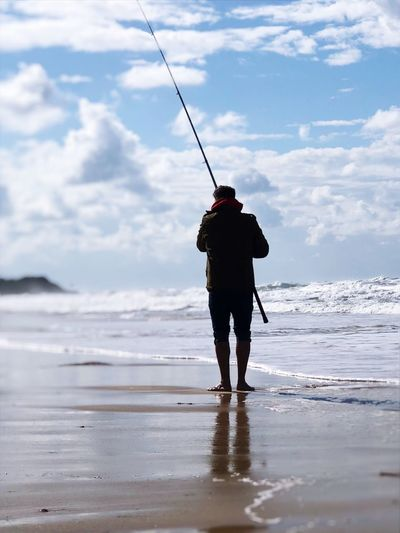 Rear View Of Man With Fishing Rod Standing At Beach Against Cloudy Sky