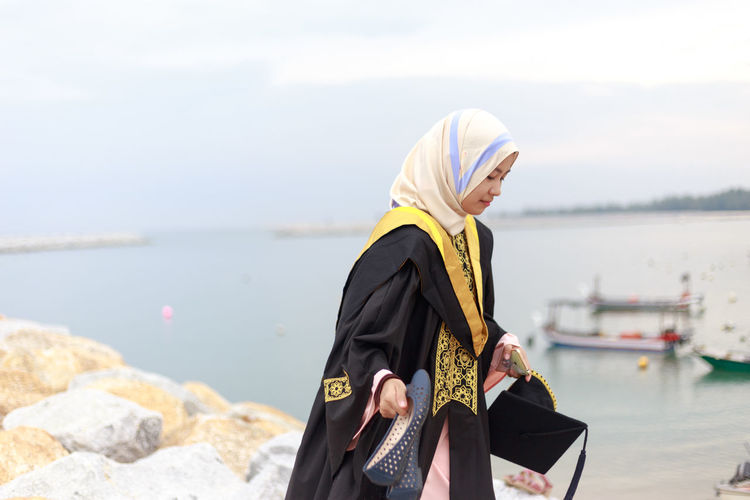 Young Woman In Graduation Gown Standing At Beach Against Cloudy Sky