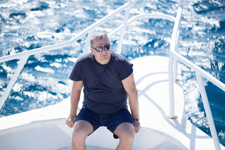 Boat Caucasian Cruise Handsome Man Middle-aged Muscular Ocean Prow Railing Relaxing Ship Sitting Sparkling Summer Sunglasses Sunshine Transport White Yacht