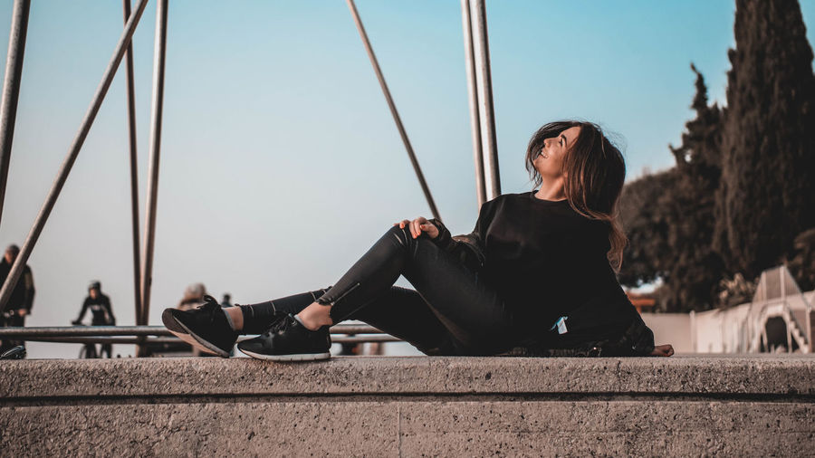 Woman sitting against sky