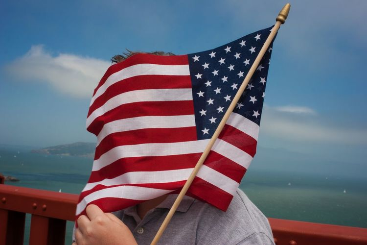 Person face covered with amercian flag against sea
