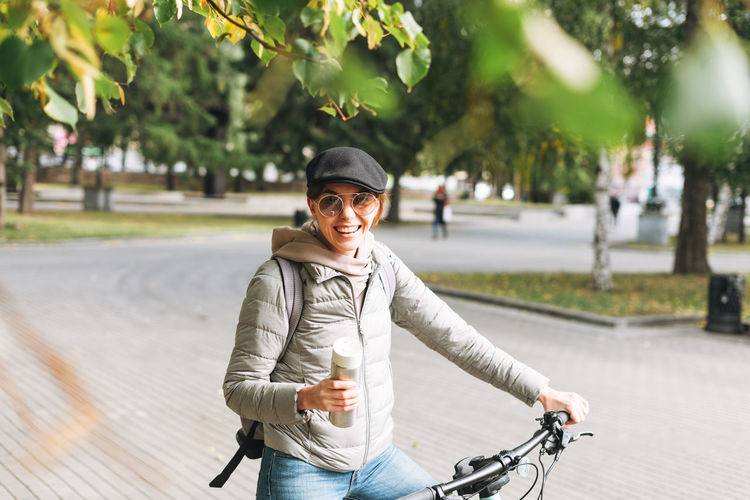 Portrait of smiling man riding bicycle on city