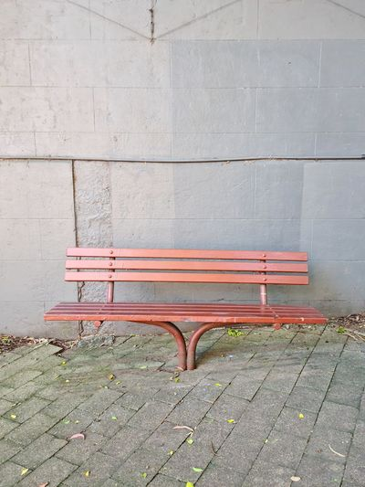 Empty bench on footpath against wall