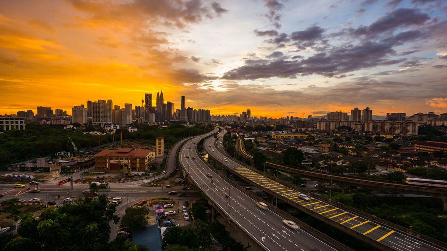 High angle view of street amidst buildings against sky during sunset