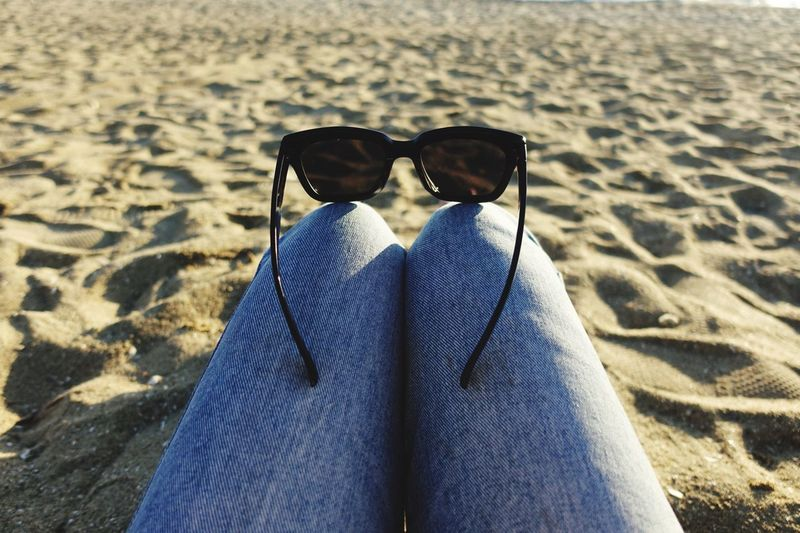 Low section of person wearing sunglasses on sand