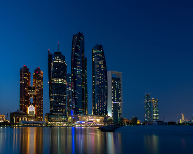 Illuminated buildings in city against sky at night in abu dhabi