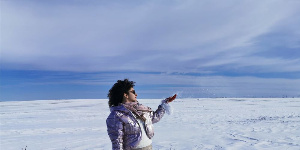 Full length of woman standing on snow covered landscape against sky