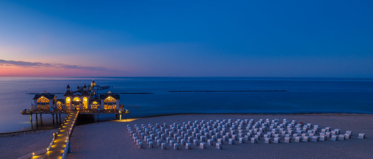 Illuminated stilt houses with pier over sea against blue sky