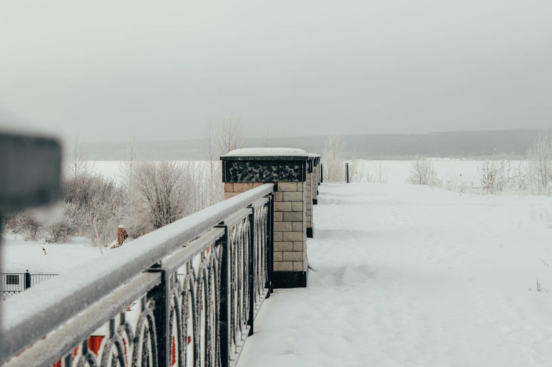 Snow covered railing against sky during winter