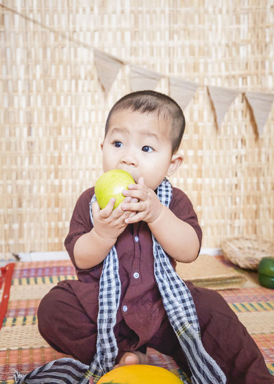 Cute baby boy eating granny smith apple while sitting at home