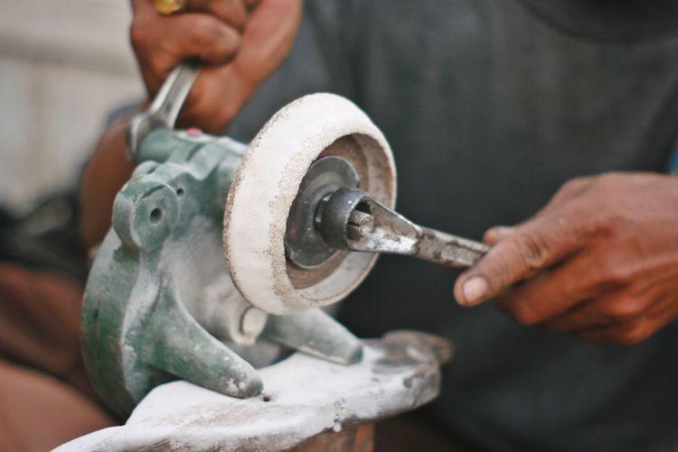 Low section of man repairing power tool in workshop