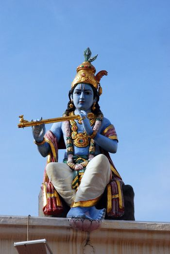 Low angle view of krishna statue against blue sky
