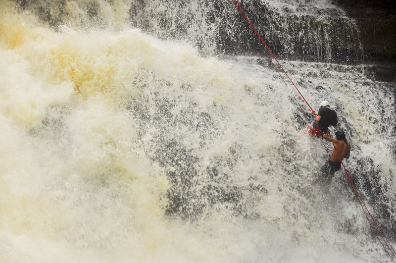 People climbing up waterefall