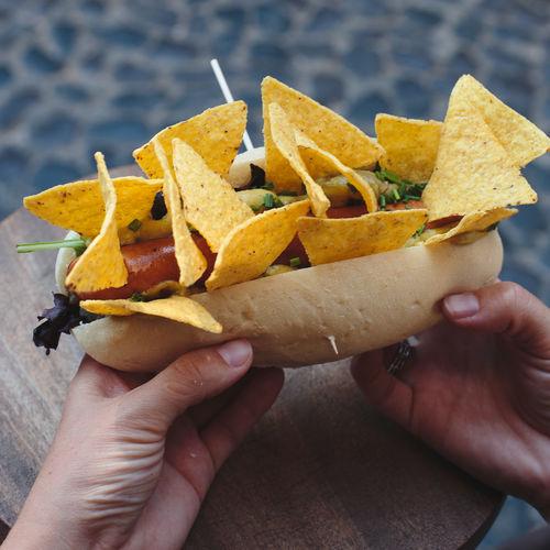Cropped hand holding hot dog