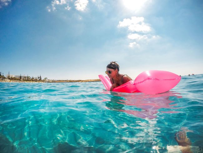 Cyprus Pink Adult Beach Blue Day Floating On Water Holiday Inflatable  Inflatable  Leisure Activity Lifestyles Nature One Person Outdoors Real People Sea Sky Sunlight Swimming Pool Trip Vacations Water Waterfront Young Adult