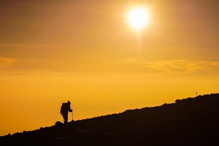 Silhouette hiker at mt fuji against orange sky during sunset