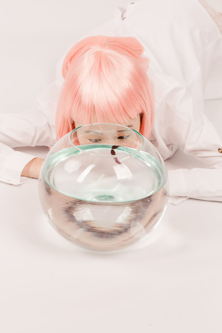 Close-Up Of Woman By Fish Swimming In Glass Bowl On Floor
