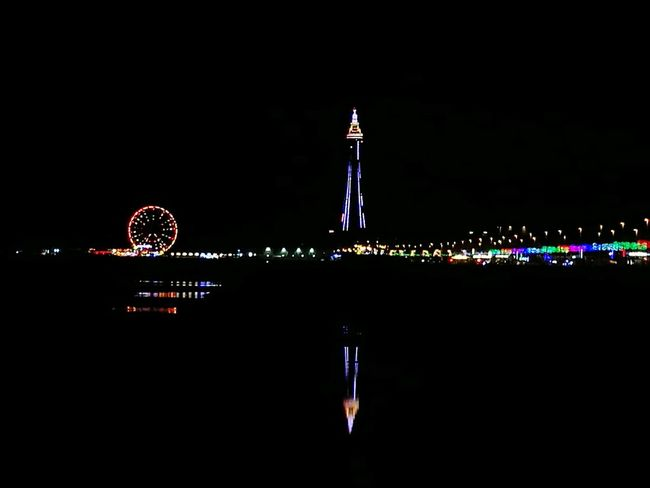 Handheld Phone Photography Blackpool Promenade Blackpool Illuminations Blackpool Tower Central Pier Illuminated Night Water Waterfront Reflection Architecture Dark Skyscraper Sea Sky Calm Scenics Tall Modern No People Tranquility Multi Colored Tranquil Scene Ocean