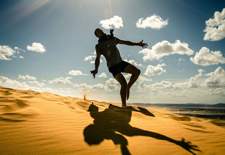 Man in the desert, happy and jumps, jumping in the desert celebrating her freedom