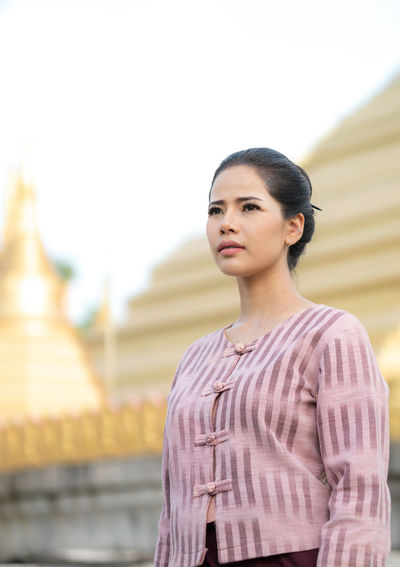 Low angle view of young woman standing against temple