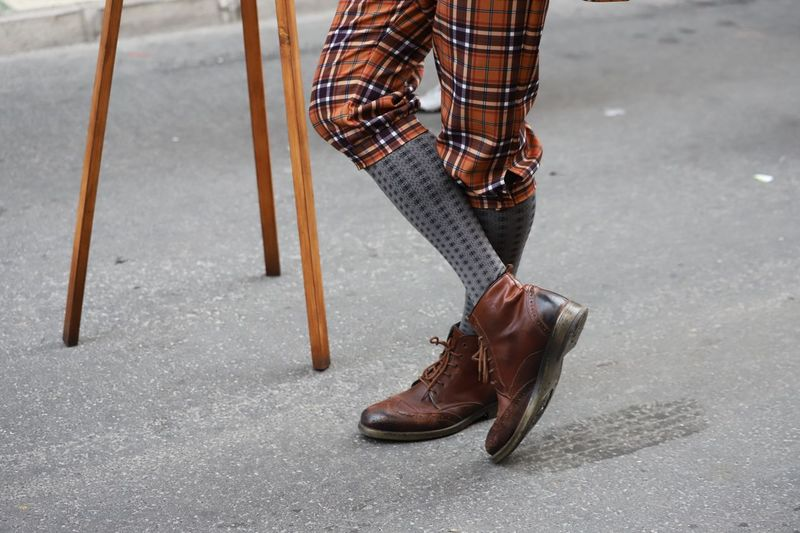 Low section of person wearing shoes while standing on road