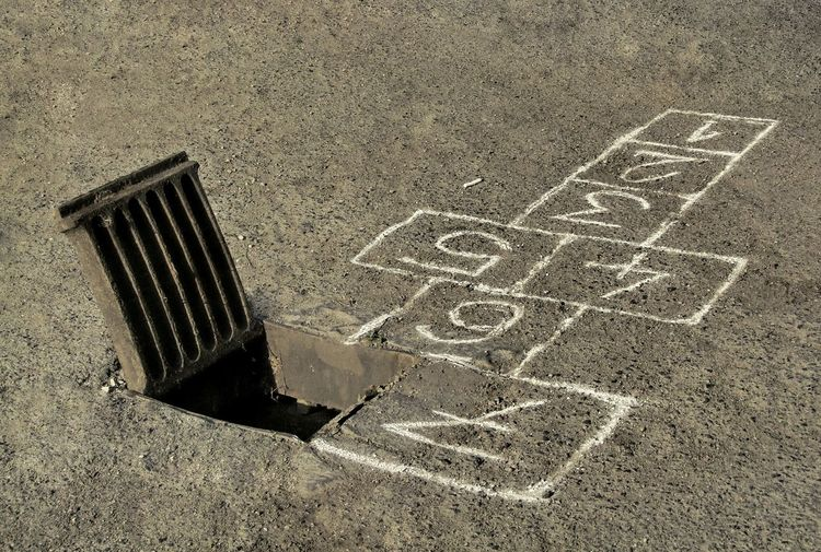 High angle view of hopscotch board drawn by manhole on street