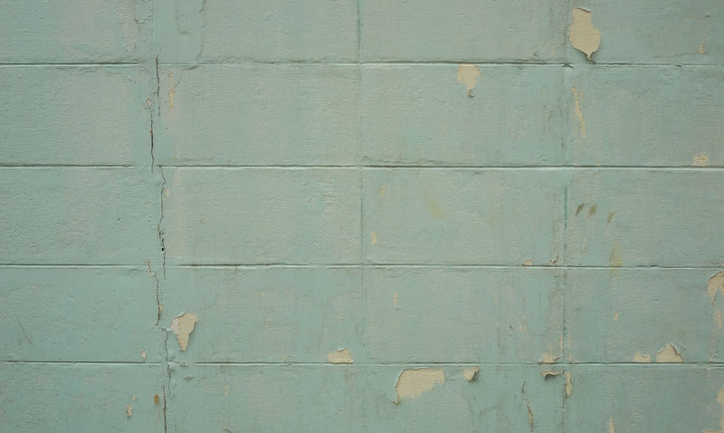 Concrete or cement block wall in broken condition with light blue color and chipping paint, selective focus. Abrasive Construction Aged Architecture Backgrounds Block Brick Broken Cement Chipping Paint Cracked Damaged Exhausted Exterior Design Fences Outdoors Pattern Rough Textured  Weathered