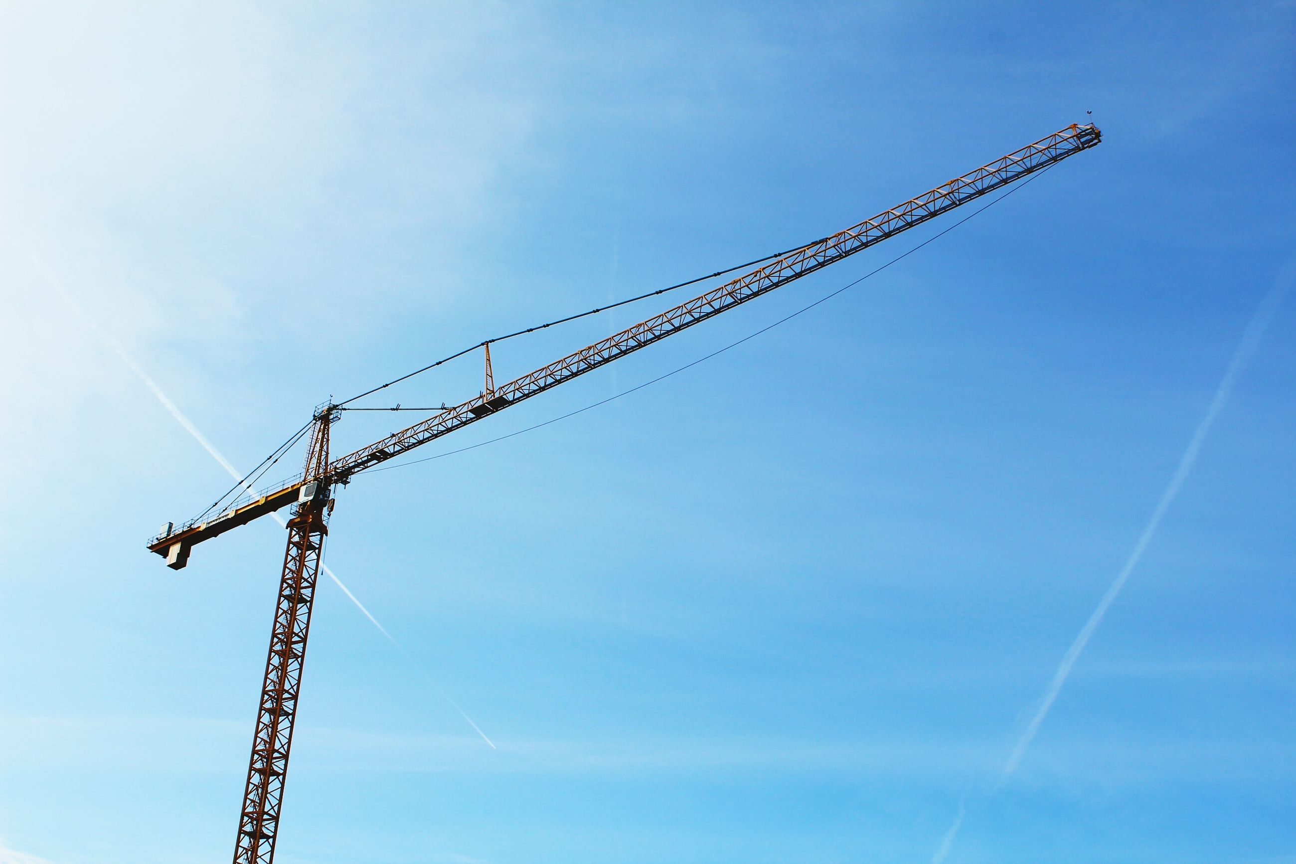 low angle view, crane - construction machinery, fuel and power generation, development, technology, construction site, sky, electricity, crane, power supply, connection, electricity pylon, construction, blue, outdoors, power line, no people, day, industry, clear sky