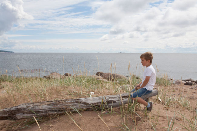 Boy alone at the sea shore Adult Beauty In Nature Blond Hair Child Childhood Cloud - Sky Day Freedom Full Length Getting Away From It All Happy Boy Horizon Horizon Over Water Lake Leisure Activity Loneliness Nature One Man Only One Person Outdoors People Scenics Sky Watching Water