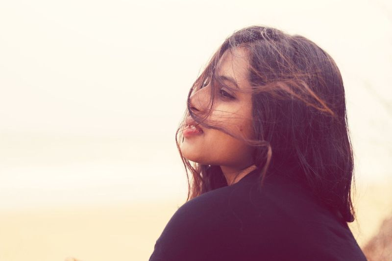 Beautiful young woman with tousled hair against sky