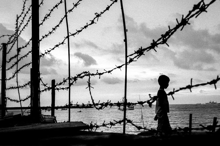 Silhouette boy standing by fence against sky