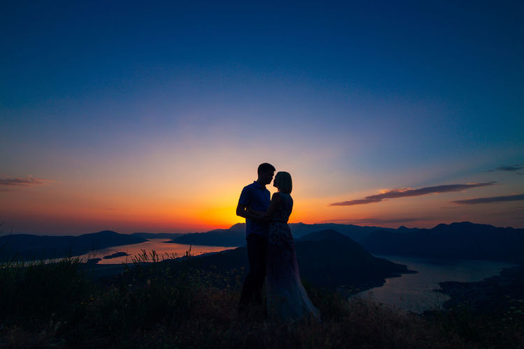 Couple kissing against sky during sunset