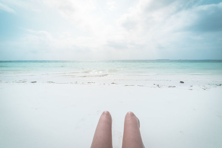 Low section of person on beach against sky