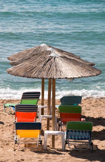 Chairs on beach against sea