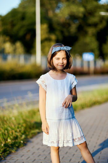 Portrait of girl standing on footpath in park