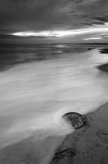 Concept alarm clock on beach of island, malaysia. Fine art black and white. Blackandwhite Fine Art Photography Long Exposure Wallpaper Background Malaysia Concept Wall Clock Water Wave Sea Beach Low Tide Sand Sunset Moon Sky Horizon Over Water Seascape