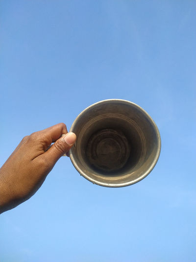 Low angle view of human hand against clear blue sky