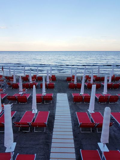 Sea Beach Horizon Over Water Red In A Row Chair Outdoors Sand Tranquility No People Day Arrangement Scenics Vacations Large Group Of Objects Sky Water Beauty In Nature Nature Clear Sky Liguria, Italy Travel Destinations Alassio Liguria Vacations Summertime