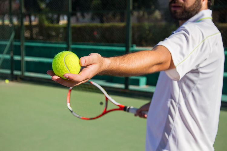 Professional tennis player offering tennis ball to play the game. Athlete Man Set Activity Ball Beared Court Give Hand Holding Leisure Activity Match - Sport Offer One Person Player Playing Professional Racket Sport Sportswear Standing Tennis Tennis Ball Tennis Racket Young Adult