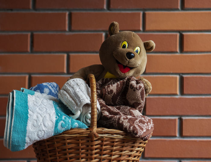 Close-up of stuffed toy against brick wall
