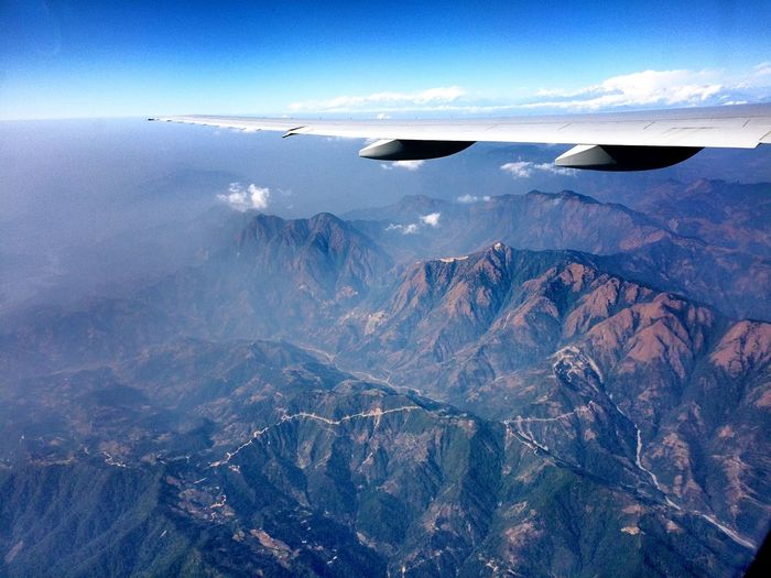 Cropped image of airplane wing over rocky mountains