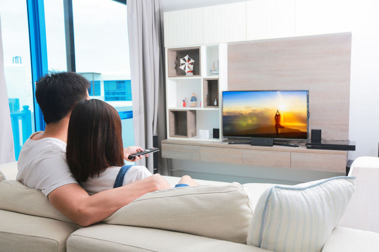 Rear View Of Couple Watching Television While Sitting On Sofa At Home