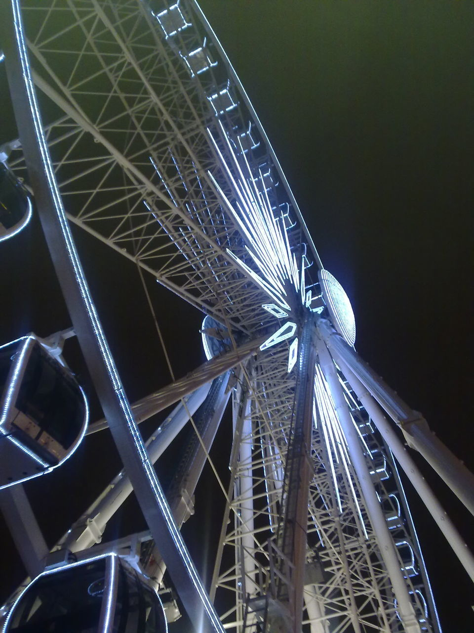 Low Angle View Of Ferris Wheel Against Dark Sky
