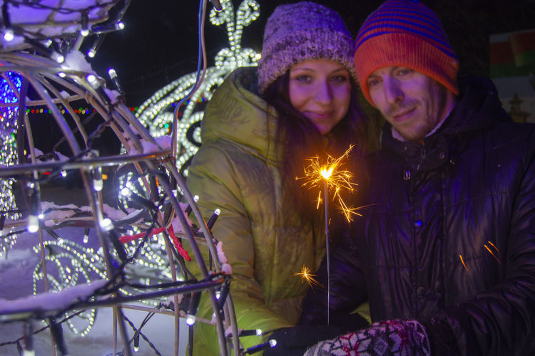 Two People Illuminated Night Winter Togetherness Real People Couple - Relationship Bonding Portrait Warm Clothing Celebration Emotion Leisure Activity Love Men Smiling Women Young Adult Positive Emotion Heterosexual Couple Sparkler Sparkler In Hand Christmas Decoration Christmas Lights Emotions
